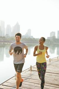 man and woman jogging with cityscape in background